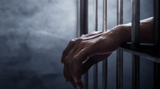 A photo of a man's hands reaching through prison bars.