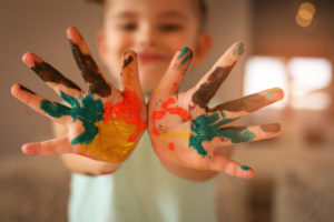 A happy boy with paint all over his hands.