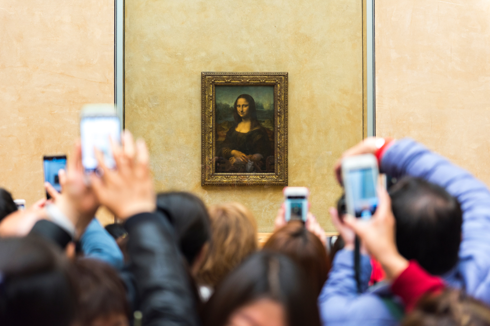 "Spectators take photos of Leonardo da Vinci's ""Mona Lisa"" at the Louvre Museum in Paris, France."