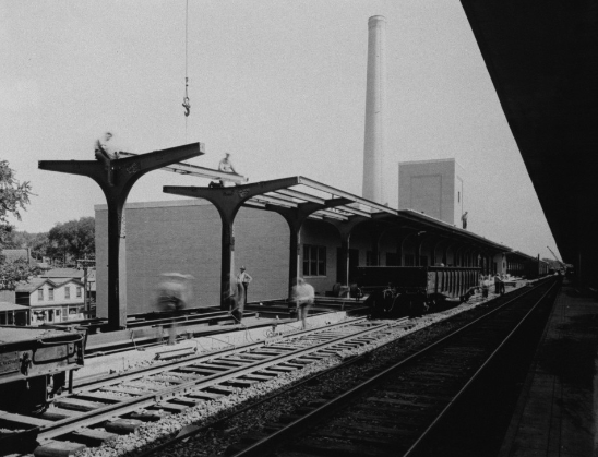 A black and white photo of a rail platform.