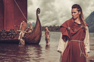 A photo of a Norse woman standing in front of a Viking ship.