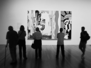 A photo of people looking at a painting at the De Young Museum in San Francisco.