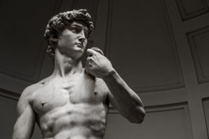 """A sculpture of a very fit man. The sculpture is called """"David"""" by famed artist Michelangelo."""