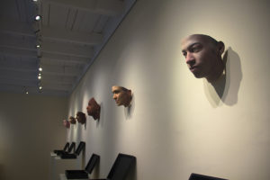 "An assortment of masks hung up on the wall inside an art gallery. The masks are part of an exhibition called ""Stranger Visions"" by Heather Dewey-Hagborg."