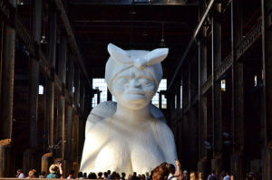 """A giant sculpture of a nude black woman. The sculpture was created by Kara Walker and is titled, """"A Subtlety, or the Marvelous Sugar Baby?"""""""