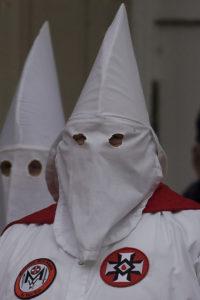 Two KKK members wearing white hoods.