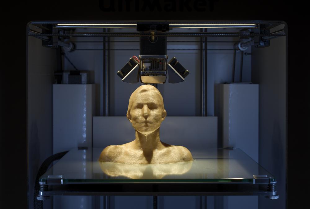 A 3D printer manufacturing a golden female sculpture.