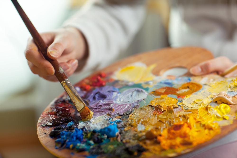 An artist mixes various paint colors on a palette.